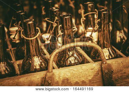 Old Drink Bottles in the Wooden Crate. Vintage Glass Bottles. Sepia Color Grading.