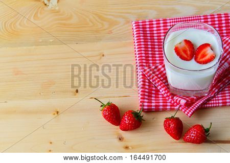 Yogurt and Strawberry in a glass cup on a red tablecloth. On the background of wood. heart in yogurt with valentine 's day.