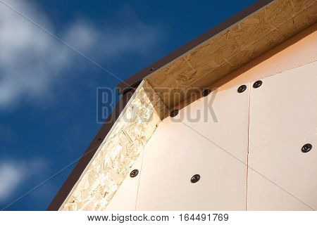 Roof of a country house covered with brown metal tile and wall with insulation closeup against blue sky with white clouds