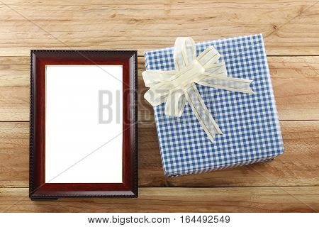 Blue gift box place near Brown wooden frame on the wood floor in concept of Christmas and New year.