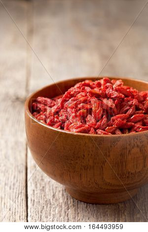 Goji berries in a wooden bowl on the old wooden background