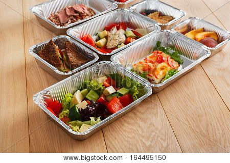 Healthy eating, diet concept. Take away organic restaurant food. Weight loss nutrition in foil boxes. Vegetable salads and whole grain sandwiches with cheese at white wood