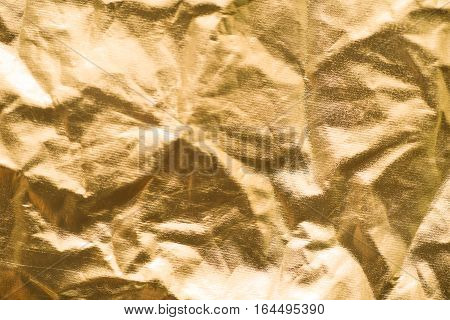 Crumpled gold paper with breaks and irregularities. Golden abstract  background