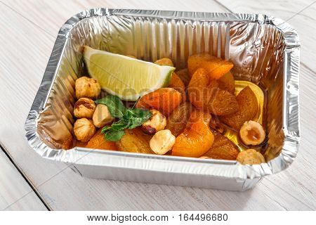 Healthy snack or dessert. Sweet dried apricots with hazelnuts and honey closeup in foil delivery box. Vegetarian diet. Fresh prepared food take away, natural organic meals