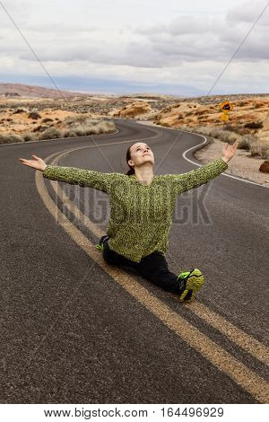 Young woman doing split on the road at Valley of Fire State Park southern Nevada USA