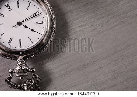 open pocket watch and chain lie on a light wooden table background arrow on the clock