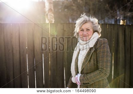 Beautiful senior woman on a walk in sunny winter nature, standing against wooden fence.