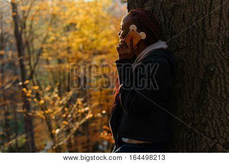 Woman talking by phone in the autumn park at sunset.Girl standing near tree and looking at the yellow leaves