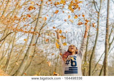 happy attractive pretty girl playing with leaves, enjoying warm autumn day in park. Have fun in autumn