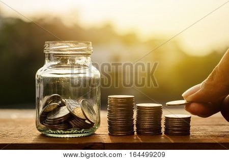 Hand with rows of coins and account for finance and banking concept Hand with money coin stack growing business Saving money concept