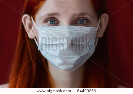 red-haired girl with a medical mask on a red background woman doctor woman with intense look European eared girl