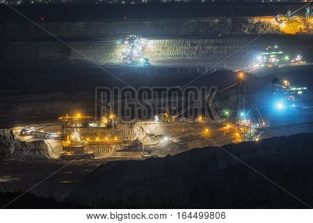 Large excavator machine in the mine at night