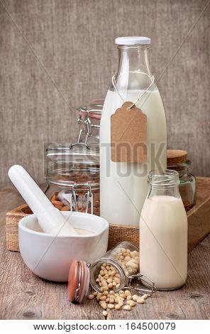 nut milk: almond cedar walnut hazelnut on the old wooden background