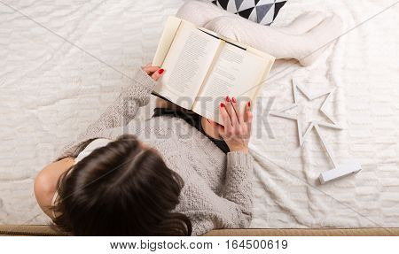 Woman Relaxing With A Book At Her Home