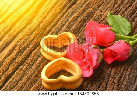 The wood hearts and three pink rose for valentines day and love under the sunlight on old bark.