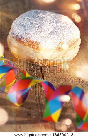 Delicious donuts on wood with colorful air streamer and bokeh for carnival and party
