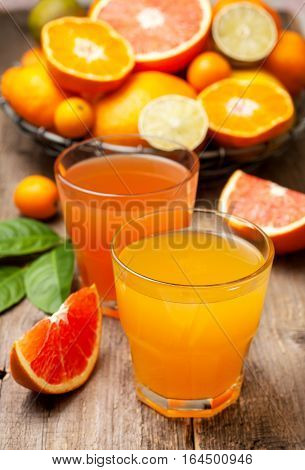 Citrus juices and fresh citrus fruit on the old wooden background. selective focus