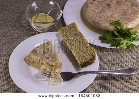 aspic from chicken meat with herbs in a white plate