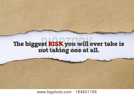 The biggest risk you will ever take is not taking one at all message written under torn paper.