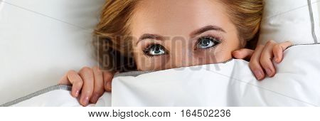 Beautiful Blonde Woman Hiding Face Under Cover Lying In Bed