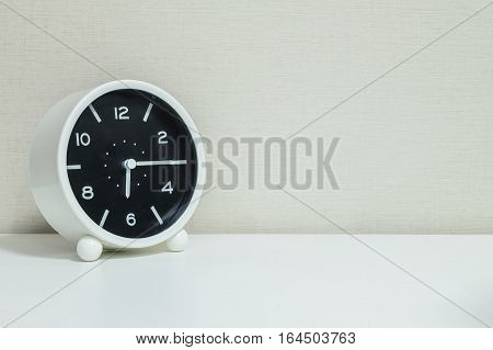 Closeup black and white alarm clock for decorate show a quarter past six or 6:15 a.m.on white wood desk and cream wallpaper textured background with copy space