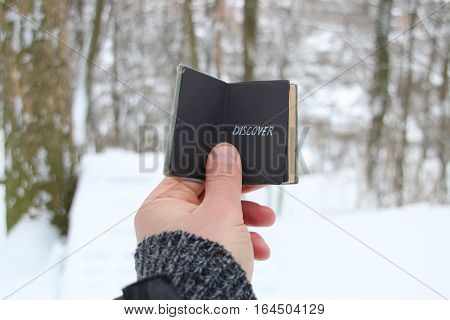 Discover or Joyrney idea. Hand holding a book with the inscription. On the background of the forest with snow-covered trees
