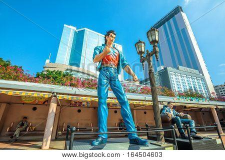 Hong Kong, China - December 5, 2016: Hui Lok and Wang Xiao Hu, statues of famous characters, in Hong Kong Avenue of Comic Stars, Kowloon Park. Urban skyline background of Tsim Sha Tsui District.