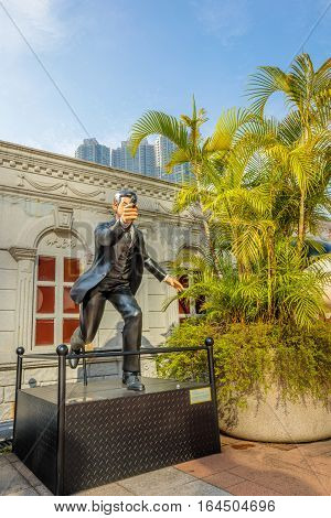 Hong Kong, China - December 5, 2016: K with gun, statues of famous characters, in Hong Kong Avenue of Comic Stars, Kowloon Park. Urban skyline and natural tree background of Tsim Sha Tsui District.