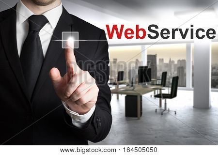 businessman in large modern office pushing button webservice