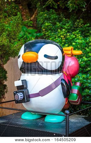 Hong Kong, China - December 5, 2016: Statue of Ding Ding Penguin and a camera with a natural combination of green leaves background. Hong Kong Avenue of Comic Stars in Kowloon Park, Tsim Sha Tsui.