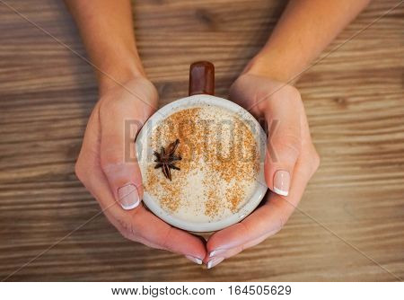 Warming Hands with Hot Mug of Cappuccino Coffee, Close up
