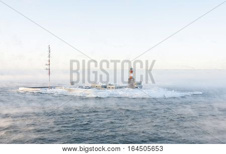 Lighthouse and telecommunication antenna on an isle in a vaporing sea at winter