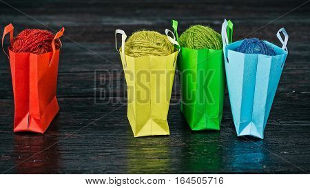 Little colorful shopping bags with yarn clews on the table. Front closeup view