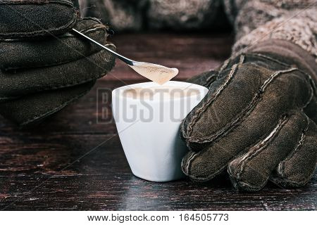 Human hands in winter sheep skin gloves holding cup of coffee and teaspoon. Front closeup view