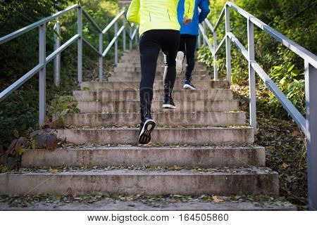 Legs of two young unrecognizable athletes running on stairs outside on colorful sunny day. Trail runners training for cross country race.