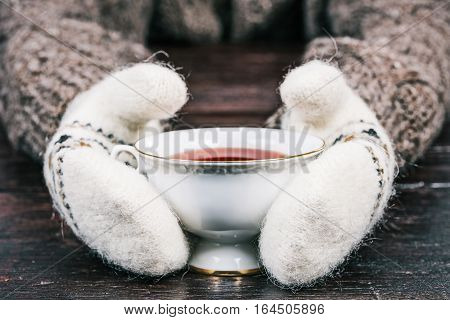 Human hands in white mittens holding white cup of cambric tea. Front view