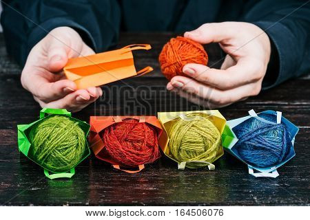 Human hands packing little colorful shopping bags with yarn clews. Concept of handy delivery of yarn and handicraft goods. Front closeup view