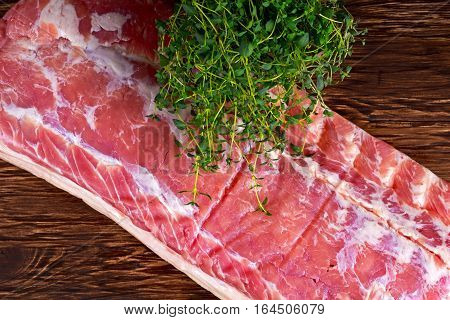 Raw whole back bacon loin with herb on wooden board.