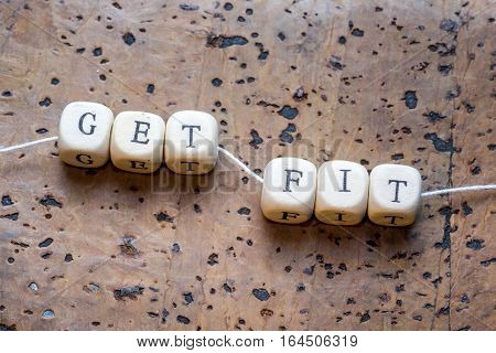 Get Fit Text Written On Wood Block On A Brown Cork Background