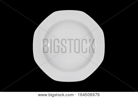 Soup deep white plate with wide shoulders and embellishment on black background from above