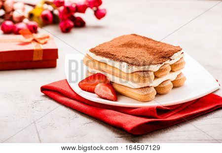 Tiramisu with strawberry and gift on the table. Valentines concept.