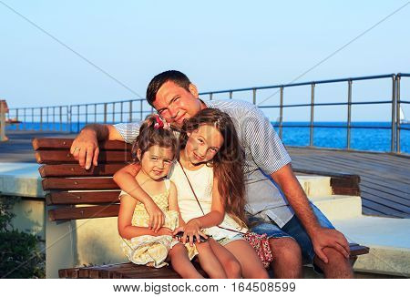 Father and Daughters Playing Together at the Beach at Sunset. Happy Fun Smiling Lifestyle. Dad with his Little Girls spending quality time Together Outdoors