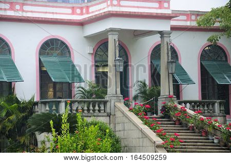 The front entrance to the historic landmark mansion at the Casa Garden on the island of Macau China on a rainy overcast day in Asia.