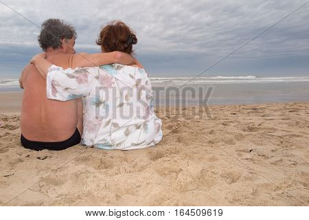 A Couple Sitting On The Beach Looks At The Hand