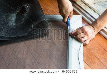 Man Replacing Ripped Old Patio Door Screen