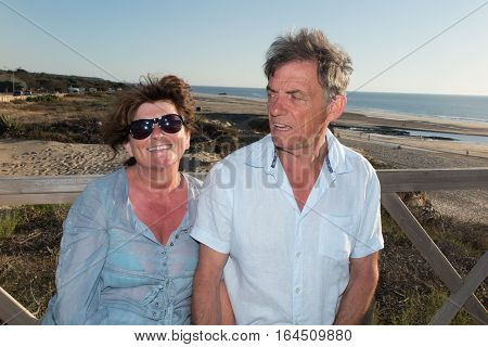 A Couple Of Seniors Summer On A Bench Next To The Beach And The Sea