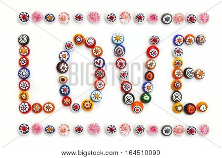The word love made of small Venetian colored glass beads. Murano glass millefiori. Overhead view. Flat lay top view