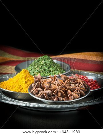 A selection of spices including star of anise pink peppercorns curry and parsley.