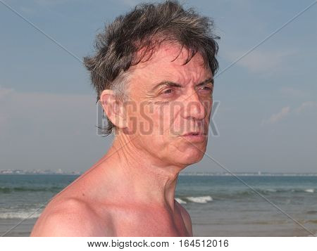 Portrait Of A Senior Man On Vacation On The Beach During The Summer