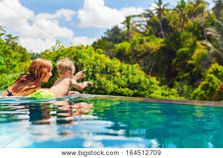 Family Bali beach holiday concept. Happy son with mother - active baby at poolside in infinity swimming pool. Summer healthy lifestyle and children water activity games and lessons with parents.